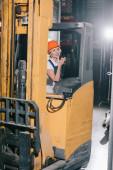 sorridente operaia seduta in carrelli elevatori, parlando walkie talkie e guardando via