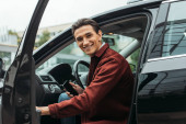 Fotografie Smiling taxi driver sitting in car with open door and holding smartphone
