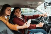 Žena cestující při pohledu na smartphone, zatímco taxikář ukazuje na silnici