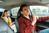 Usmívající se taxikář a pasažér s chytrým telefonem v autě