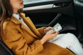 Oříznutý pohled na ženu cestující držící hotovost v taxi