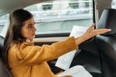 Nespokojená žena cestující s novinami na zadním sedadle taxíku