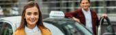 Selektivní zaměření ženy usmívá na kameru s taxikářem na pozadí, panoramatický záběr