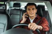 Usmívající se muž mluví na smartphone při řízení auta