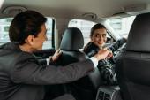 Fotografie Podnikatel ukazuje na silnici k usměvavému taxikáři