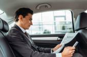 Podnikatel drží noviny a smartphone v taxi