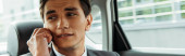 Panoramatický záběr obchodníka mluví na smartphone v taxi
