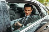 Usmívající se obchodník se dívá na hodinky v taxíku