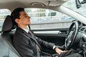 Üzletember csukott szemmel a drónautó vezetőülésén