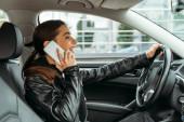Sorridente donna parlando su smartphone durante la guida di auto