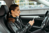 Giovane donna utilizzando smartphone sul sedile del conducente di drone auto