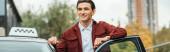 Panoramaaufnahme eines lächelnden Taxifahrers neben Auto