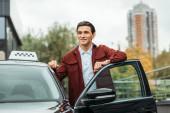 Fotografie Usmívající se taxikář vedle otevřených dveří auta