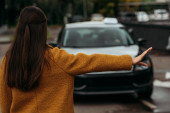 Zadní pohled na ženu chytání taxi na ulici
