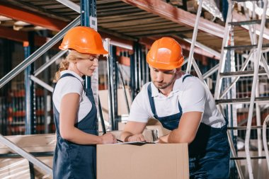 Concentrated warehouse workers looking at clipboard while standing near cardboard box stock vector