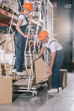 Workwoman standing on ladder and looking at loader taking cardboard box stock vector