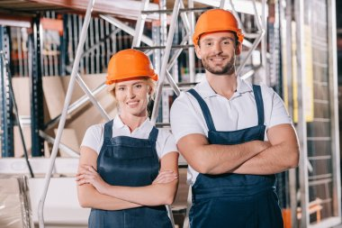 Cheerful warehouse workers standing with crossed arms and smiling at camera stock vector