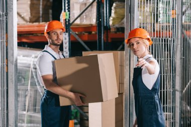 Warehouse worker holding cardboard box near workwoman pointing with hand stock vector