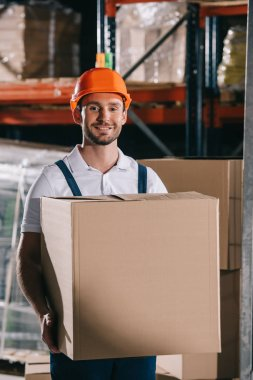 Cheerful loader smiling at camera while holding cardboard box stock vector