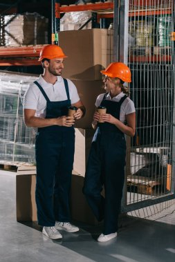 Smiling warehouse workers looking at each other while holding coffee to go stock vector