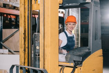 attractive workwoman sitting in forklift loader and smiling at camera