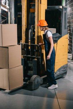 Workwoman in overalls and helmet standing near foklift loader in warehouse stock vector