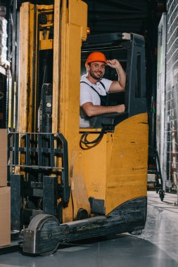 smiling warehouse worker touching helmet and looking at camera while operating forklift loader