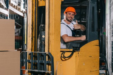 smiling warehouse worker showing thumb up and looking at camera while operating forklift loader