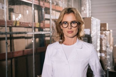 confident storekeeper in white coat looking at camera in warehouse