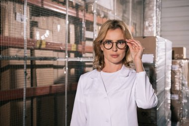 confident storekeeper in white coat touching glasses while looking at camera