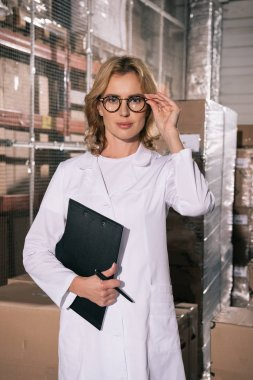 confident storekeeper holding clipboard and touching glasses while looking at camera