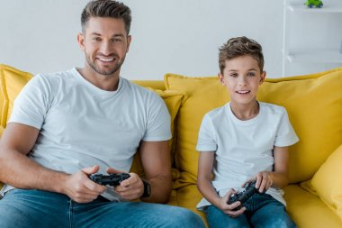 KYIV, UKRAINE - OCTOBER 2, 2019: happy father and son playing video game at home stock vector