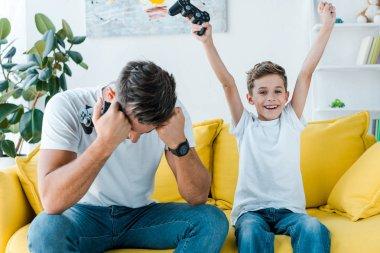 KYIV, UKRAINE - OCTOBER 2, 2019: upset father near happy son celebrating triumph while holding gamepad stock vector