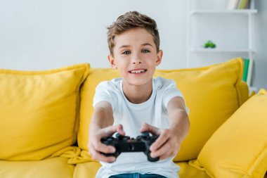 KYIV, UKRAINE - OCTOBER 2, 2019: selective focus of happy kid playing video game at home stock vector