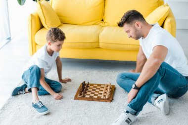 handsome father and cute son playing chess on carpet at home