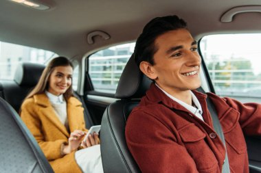 Selective focus of smiling taxi driver and woman with smartphone in car