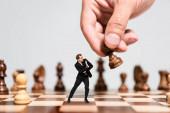 abgeschnittene Ansicht von Mann beim Schachspielen und verängstigter Marionette beim Anblick einer Figur isoliert auf grau