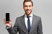 pohledný a usměvavý podnikatel v obleku drží smartphone izolované na šedé