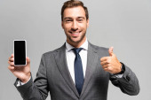 smiling businessman in suit holding smartphone and showing like sign isolated on grey
