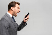 side view of handsome and angry businessman in suit shouting at smartphone isolated on grey