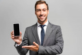 handsome and smiling businessman in suit pointing with hand at smartphone isolated on grey