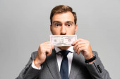 handsome businessman in suit obscuring face with dollar banknote isolated on grey