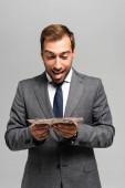 Fotografie pohledný a usmívající se obchodník v obleku drží dolarové bankovky izolované na šedé