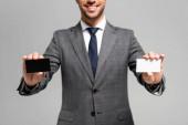 oříznutý pohled na usmívajícího se podnikatele v obleku držícího vizitky izolované na šedi