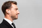 vista laterale di un uomo daffari bello e sorridente in abito ascoltando musica con auricolari isolati sul grigio
