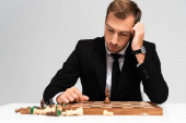 Photo sad and handsome businessman in suit looking at chessboard isolated on grey