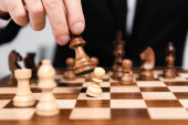 Fotografie Ausgeschnittene Ansicht von Geschäftsmann, der Schachfigur über Schachbrett hält