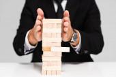 Fotografie abgeschnittene Ansicht des Geschäftsmannes im Anzug, der Blöcke spielt, Holzspiel isoliert auf grau