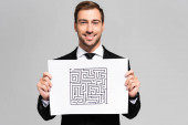 Photo smiling and handsome businessman holding paper with labyrinth isolated on grey