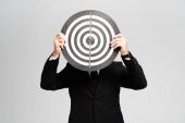 Fotografie Geschäftsmann im Anzug verdeckt Gesicht mit Dartscheibe isoliert auf grau